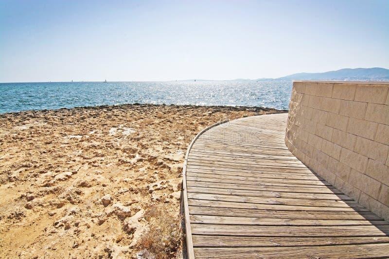 Boardwalk on beach, Majorca, Balearic Islands, Spain. Wooden boardwalk along curved seawall on waterfront in Majorca, Balearic Islands, Spain on sunny day stock photography