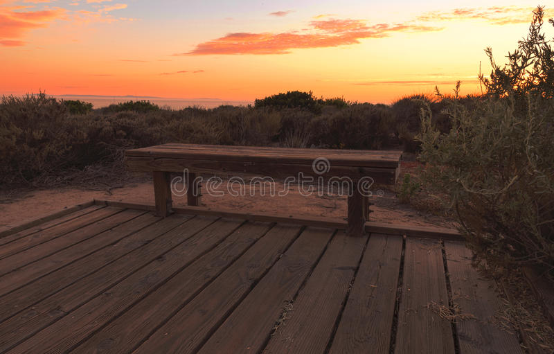Boardwalk bench at Crystal Cove beach at sunset. Boardwalk at Crystal Cove beach in California at sunset in the summer stock image