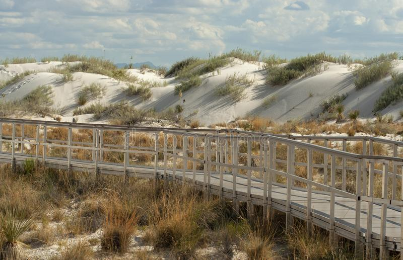Boardwalk through the  dunes at White Sands National Park, New Mexico, won. Glittering white sand dunes at White Sands National Park in New Mexico are made royalty free stock photos