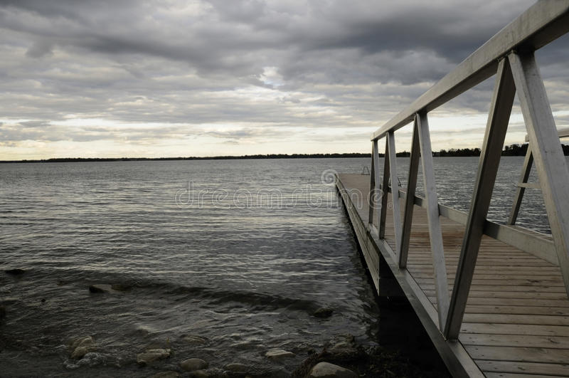 Boardwalk during dusk. A wooden boardwalk leading to lake Simcoe in Ontario stock photos