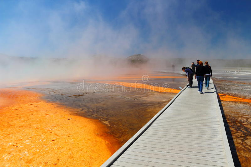 Boardwalk at Grand Prismatic Spring, Midway Geyser Basin, Yellowstone National Park, Wyoming. Tourists enjoy the colorful display of algae in the hot waters of stock image
