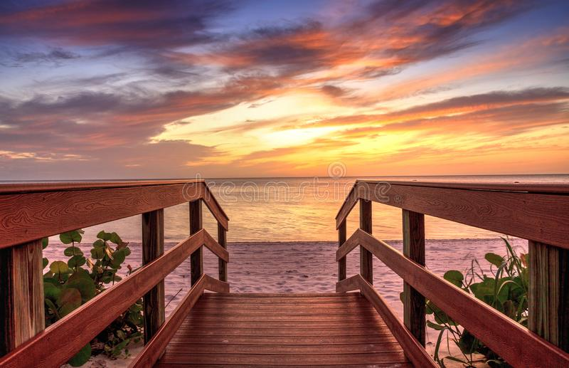 Boardwalk leading to a Sunset over North Gulf Shore Beach. Along the coastline of Naples, Florida stock photos
