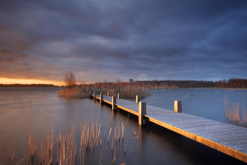 Boardwalk over a lake under stormy skies in The Netherlands. A boardwalk over a lake with an ominous sky. Photographed at sunrise stock photography