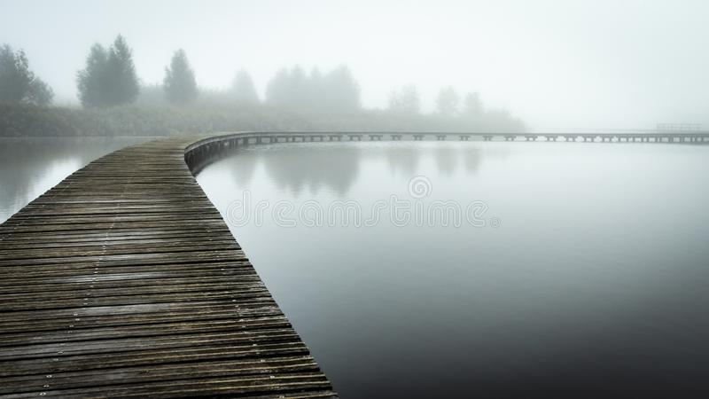 Boardwalk over still water in the fog. A wooden boardwalk in a park in Barendrecht in the Netherlands. The walkway curves away from the viewer to the right stock images