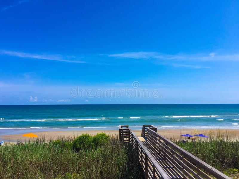 Boardwalk with sand beach and blue sky stock image