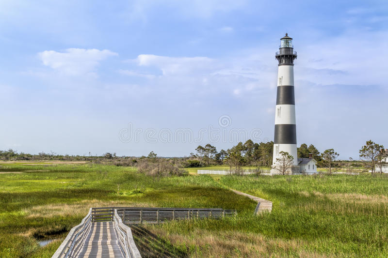 Boardwalk to Bodie Island Lighthouse. A board walk leads the eye to the historic Bodie Island Lighthouse at Cape Hatteras National Seashore on the Outer Banks of royalty free stock photography