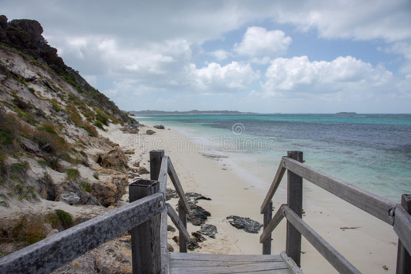 Boardwalk to Indian Ocean Beach. Boardwalk to remote beach with the turquoise Indian Ocean seascape at Rottnest Island under a blue sky with clouds in Western stock photo