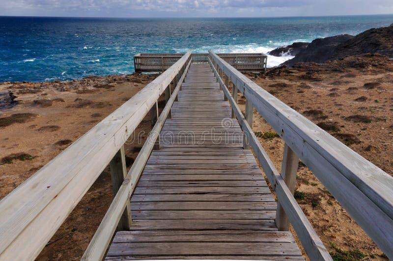 Boardwalk to platform overlooking ocean. Perspective of wooden boardwalk leading to platformoverlooking ocean on deserted coastline royalty free stock images