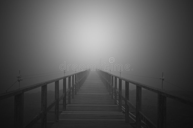 Boardwalk to the sky. A black and white view of a boardwalk appearing to fade into a light in the sky stock image