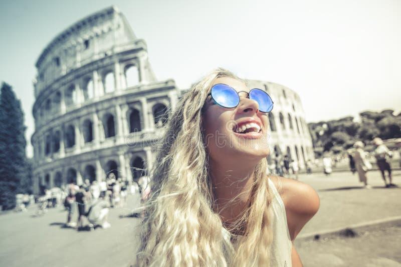 Boas festas em Roma, louro novo de sorriso na frente do colosseum em Roma em Itália fotografia de stock