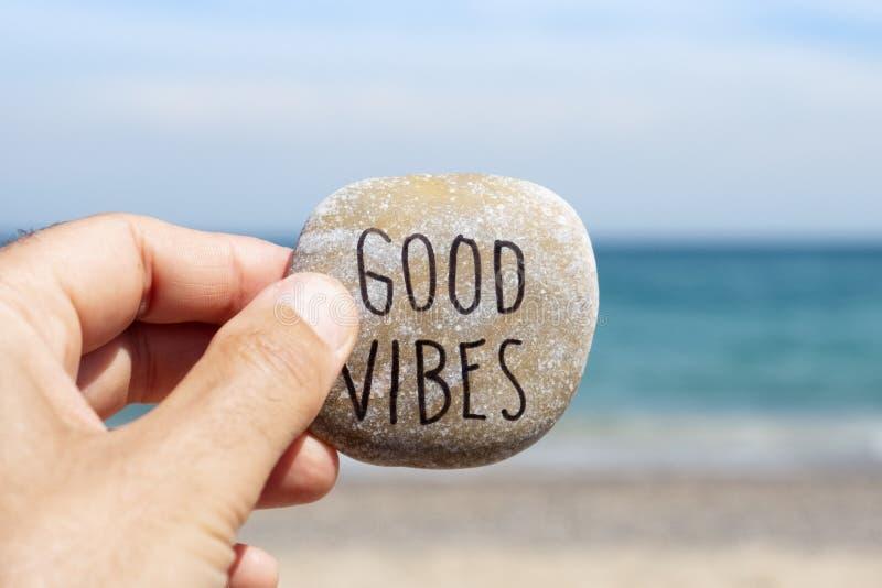 Boas vibrações do texto em uma pedra na praia imagem de stock