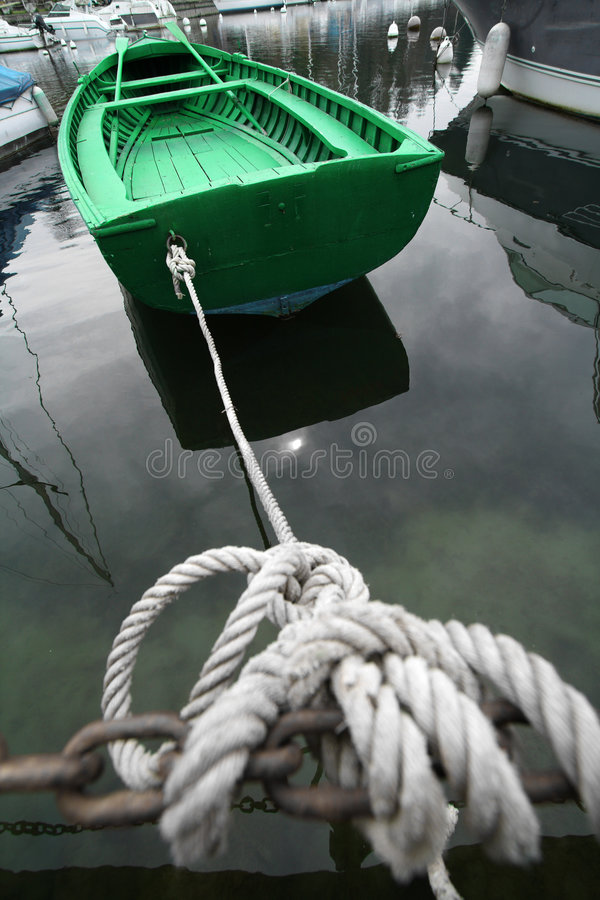 Boat. Green boat tied up with rope to a harbor. Concept: Sailing vacation royalty free stock photo