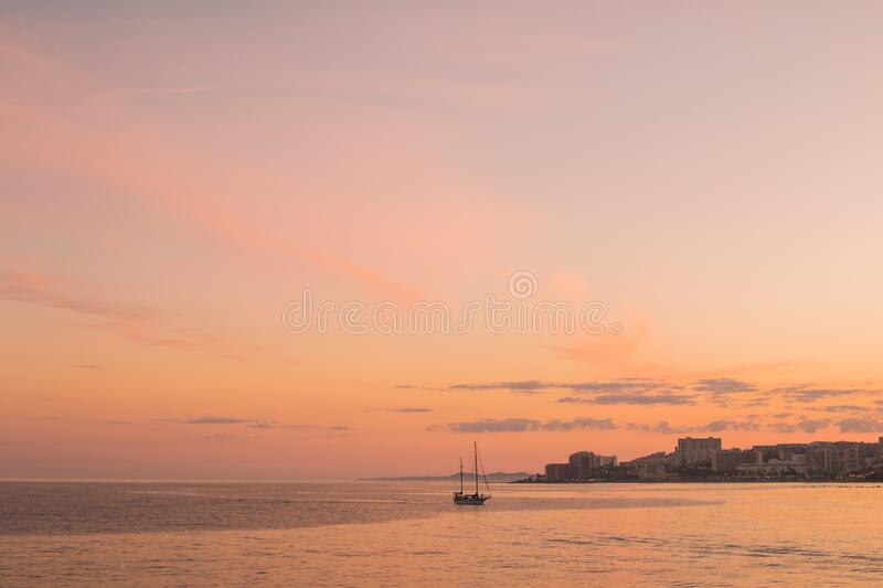 Boat along coastline at sunset royalty free stock image