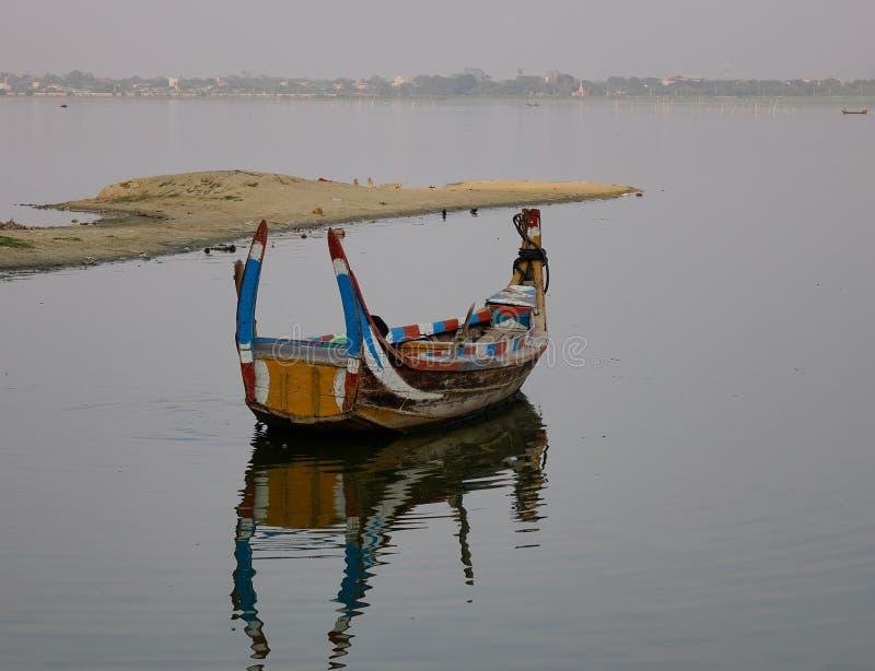 A boat on Amarapura lake at Ubein bridge. A boat waiting tourists on Amarapura lake at Ubein bridge in Mandalay, Myanmar stock photography