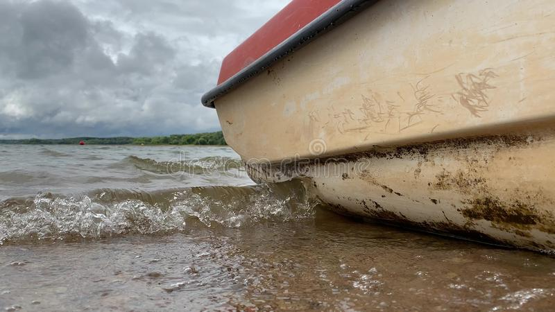 A boat anchored in harbor, dock near the water and waves lapping up against the shore and boat sides, low angle.  stock photography