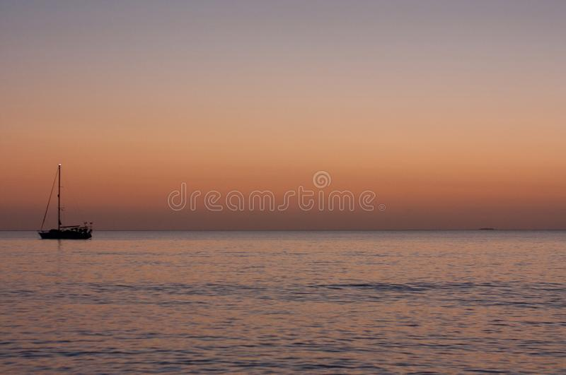 A boat anchoring near Uoleva during sunset. A boat anchoring near Uoleva, Tonga, during sunset, oceania, sand, sea, pink, vacation, blue, water, summer, tourist stock photo