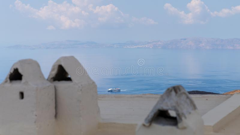 Boat approaching harbour, on aegean island of Tinos, Greece. Boat approaching the harbor of Tinos, in the mediterranean sea, in Greece. As seen over the rooftop royalty free stock photography