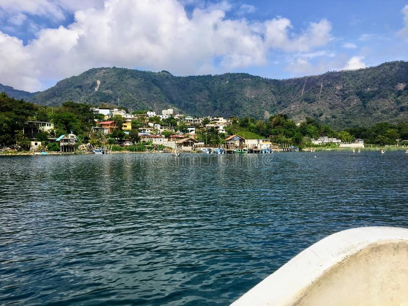 A boat approaching a small mayan village, San Juan La Laguna, on the beautiful clear waters of Lake Atitlan in Guatemala. Central America. This is a popular stock photo