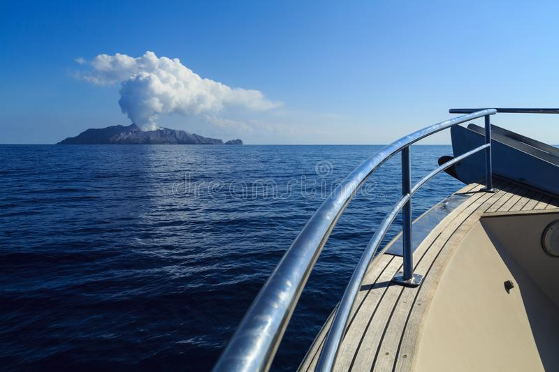 Boat approaching White Island, an active volcano in New Zealand stock photography