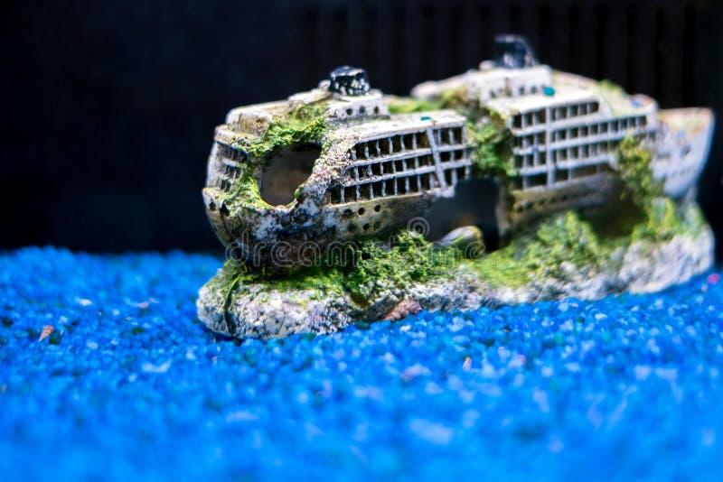 Boat aquarium accessories with blue gravel stock image
