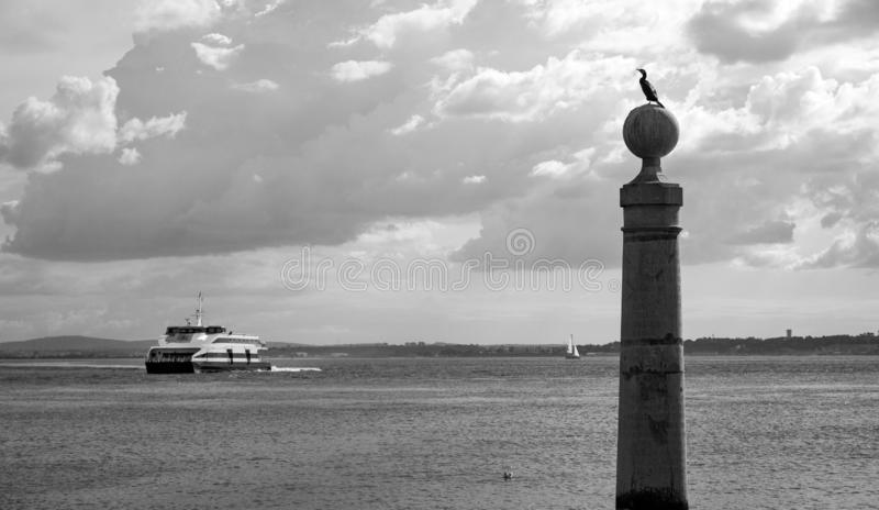 Boat arriving to harbour with column and seagulls black and white. Seagulls in port with ship monochrome. Navigation and sea transportation concept. Seascape stock image