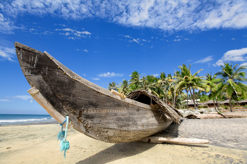 Boat on the beach. Fisherman boat on the sunny beach with green palm near ocean royalty free stock photos