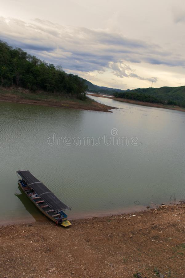 Boat sitting on shore of a lake in National Park, Thailand royalty free stock photo