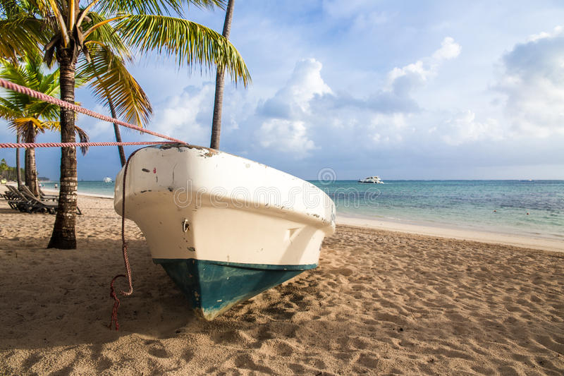 Boat on the beach, Caribbean Sunrise. Caribbean sunrise on sandy beach with palm trees and boat royalty free stock images