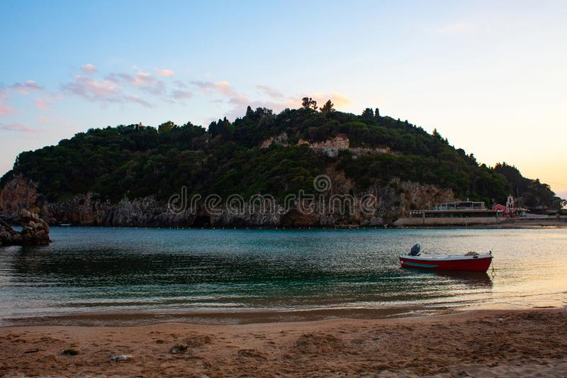 Boat on the beach with green island in the background. Fishing boat parked on the sandy beach. stock images