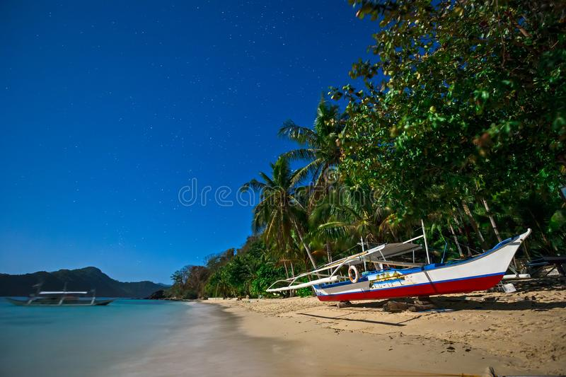 Boat on the beach in the moonlight stock photos