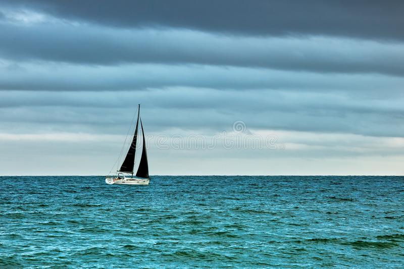 Boat with black sails on the sea in stormy weather royalty free stock photography