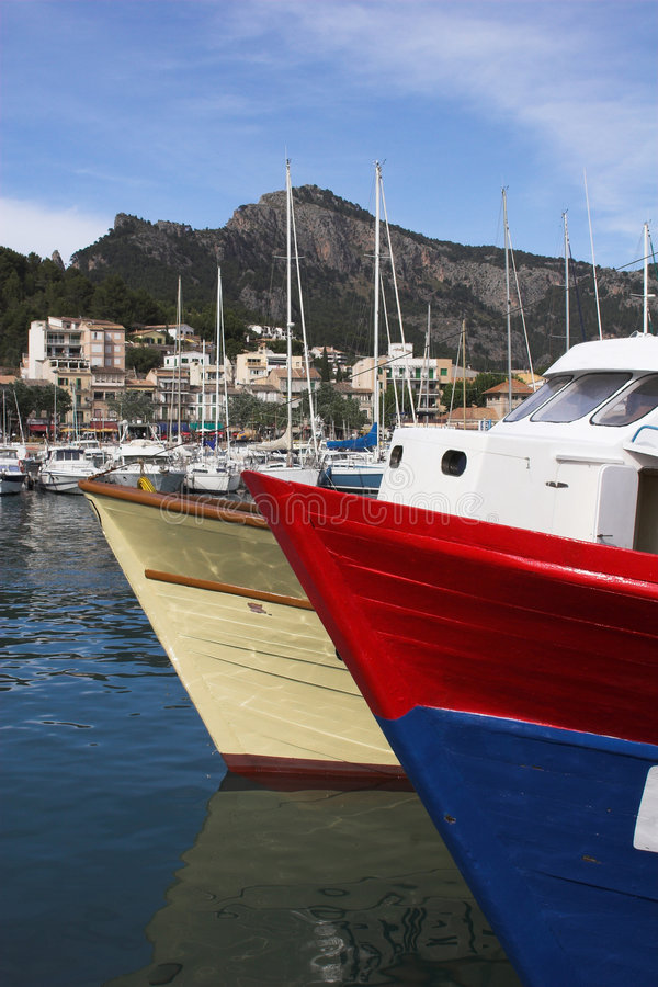 Boat bows. In port with mountain backdrop on sunny day royalty free stock photo