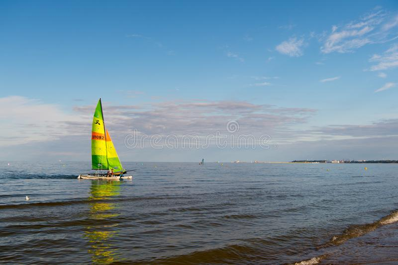 Boat with bright sail sailing in sea of Gdansk, Poland. Sailboat on water on sunny blue sky. Summer adventure and active stock photo