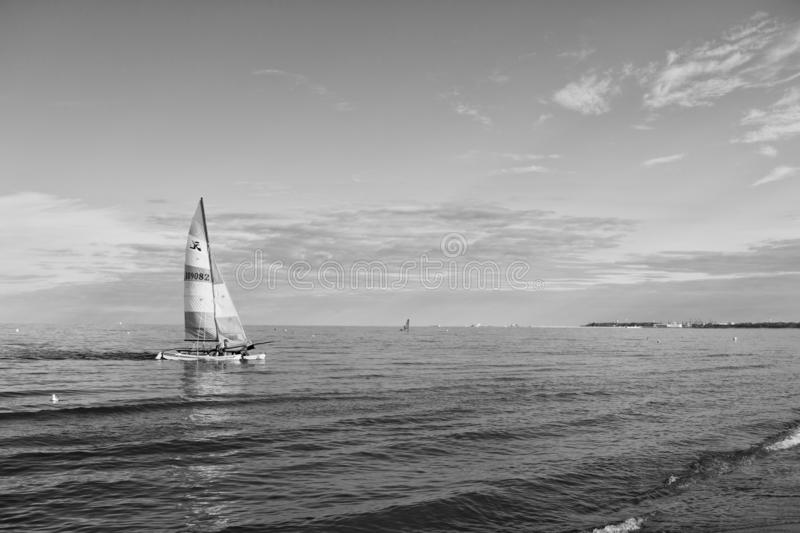 Boat with bright sail sailing in sea of Gdansk, Poland. Sailboat on water on sunny blue sky. Summer adventure and active royalty free stock photography