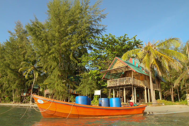 Boat and bungalow on the shores of the sea stock images