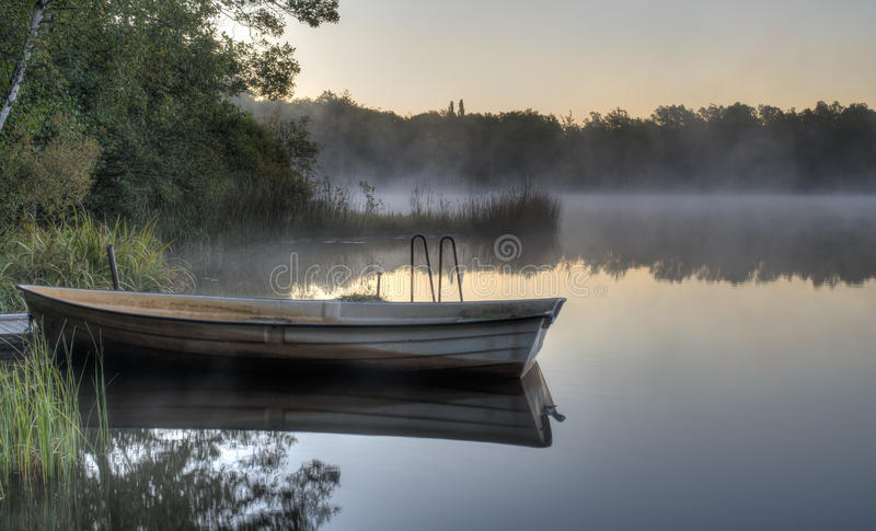 Boat on a calm lake. A rowboat by a pier on a calm Swedish lake with mist drifting across. It is early morning and everything is quiet royalty free stock photography