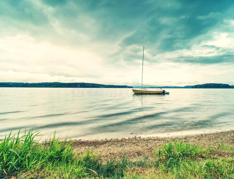 Boat on calm water. Yacht on water near the coast. Empty yacht. And blue silent water, yachting, wind, white, wave, voyage, vessel, vacation, tropical, travel stock image
