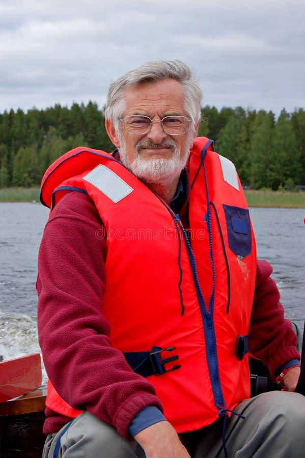 Boat captain. Elderly man driving a speedboat stock photos