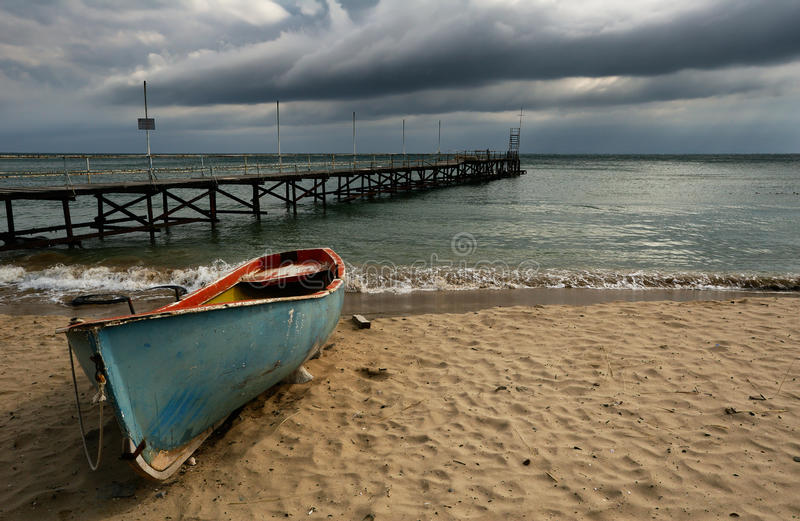 Boat on cloudy beach stock images