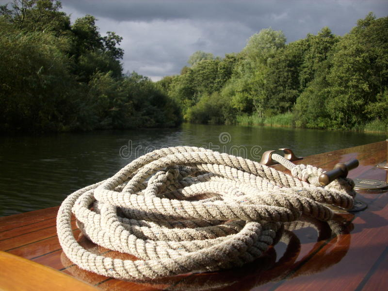 Boat with coiled rope. Wooden boat with rope coiled on bow on a river surrounded by trees with grey blue sky stock image