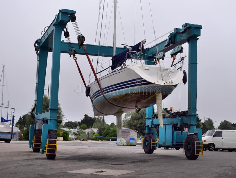 Boat crane lifitng a motorboat in the marina stock images
