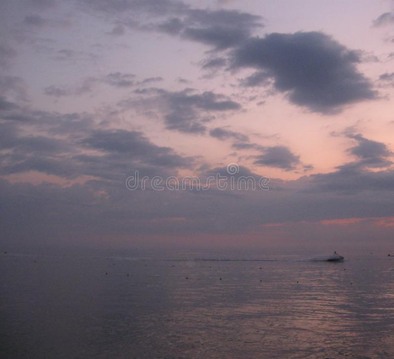 Between the Sea and the Sky. Boat crossing the sea along the horizon line under the lilac clouds at pale pink sunset stock images