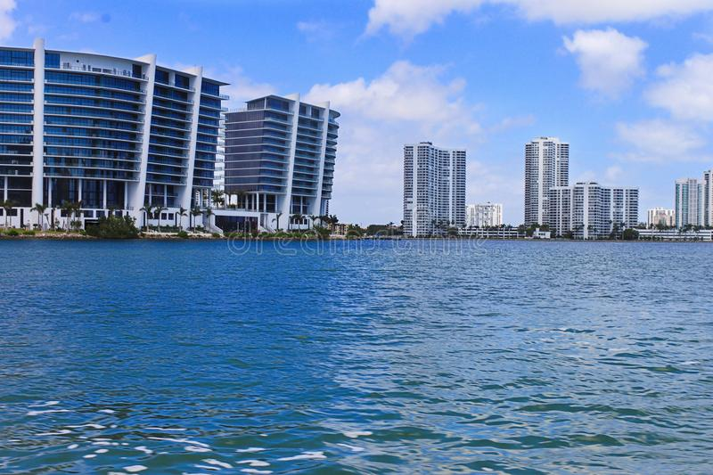 Boat cruise in sea near luxury buildings and skyscrapers. Modern houses with luxury apartments and waterway. royalty free stock photography