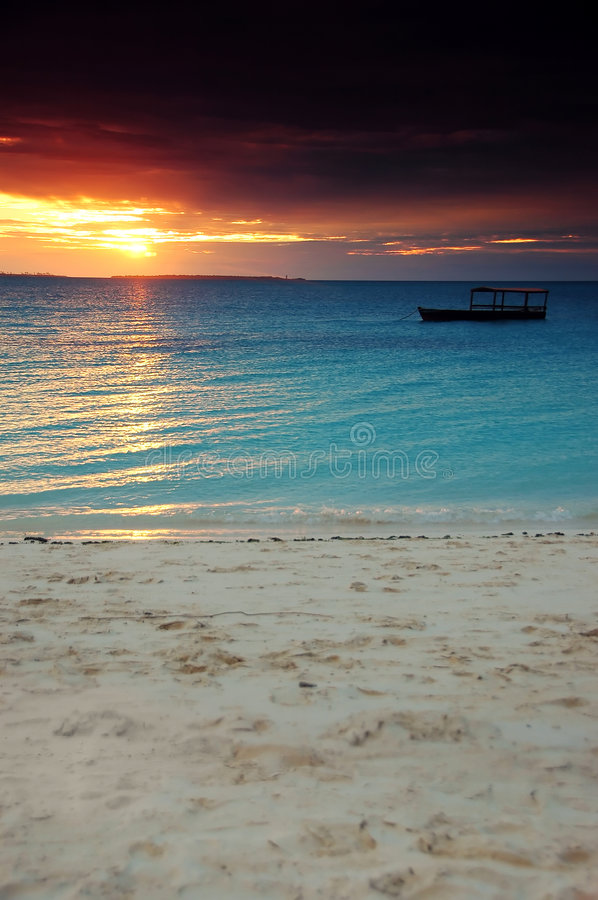 Boat in a dark sunset - Zanzibar. Boat in a dark sunset in Zanzibar (Tanzania) with a special colorful sunset and white sand stock images