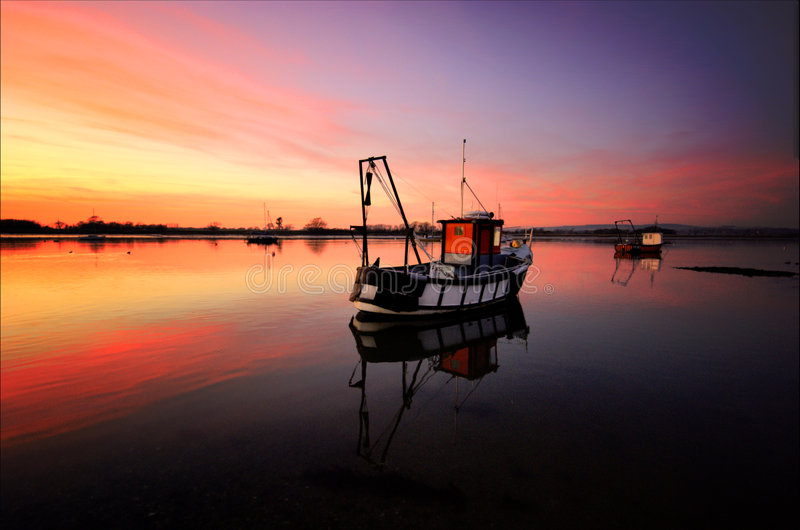 Boat on Dell Quay Harbour Waters. Boat on the waters in Dell Quay Harbour, West Sussex at Sunset stock images