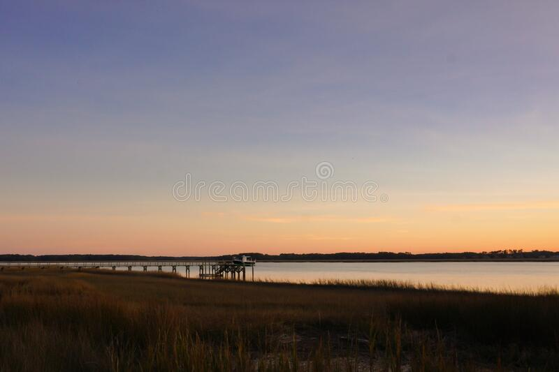 A boat dock leads out from the marsh into the waters of a river in the low country of South Carolina at sunset; copy space. Landscape view royalty free stock photo