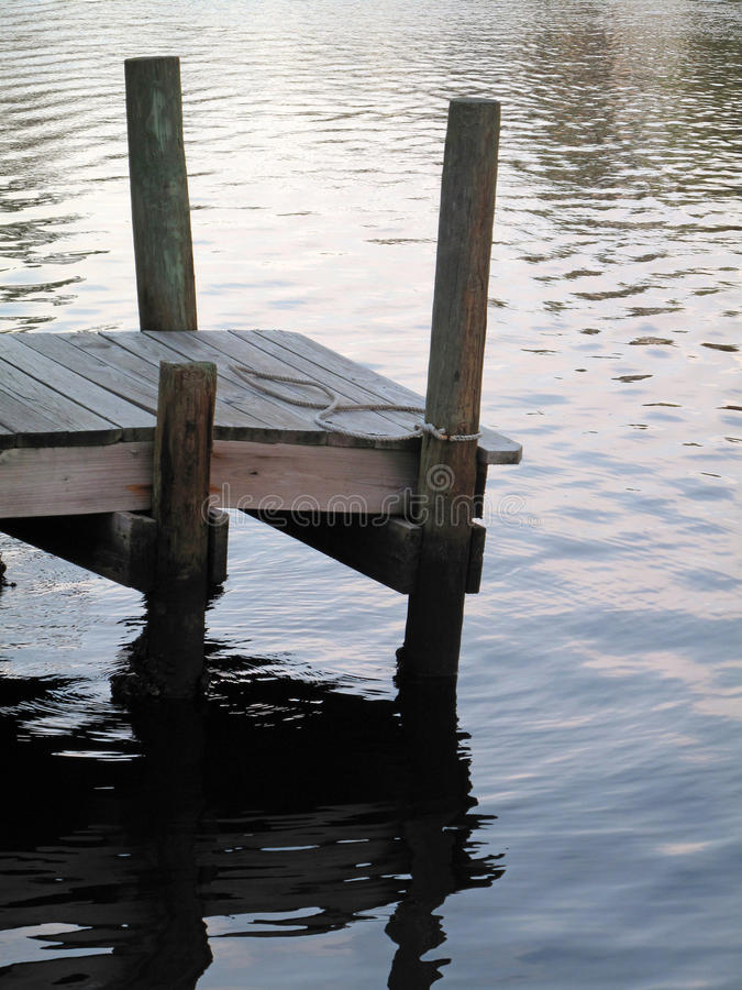 Boat Dock Reflection. A wooden boat dock with a soft rippled water reflection stock photos