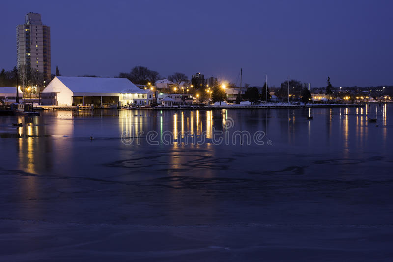 Boat docks and harbor lights reflecting in partially frozen lake. Early morning stock photography