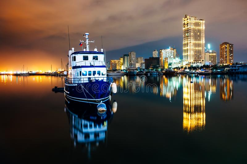 A boat docks in Manila Bay with a background of the Manila skyline royalty free stock photography