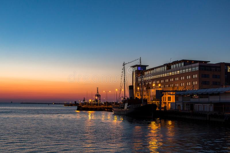 Boat and dockside buildings in Malmo harbor at sunset stock photography